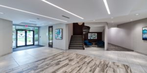 The lobby of 2301 Rexwoods Drive featuring contemporary high contrast design with pale marble floors, a contrasting dark staircase and recessed lighting.